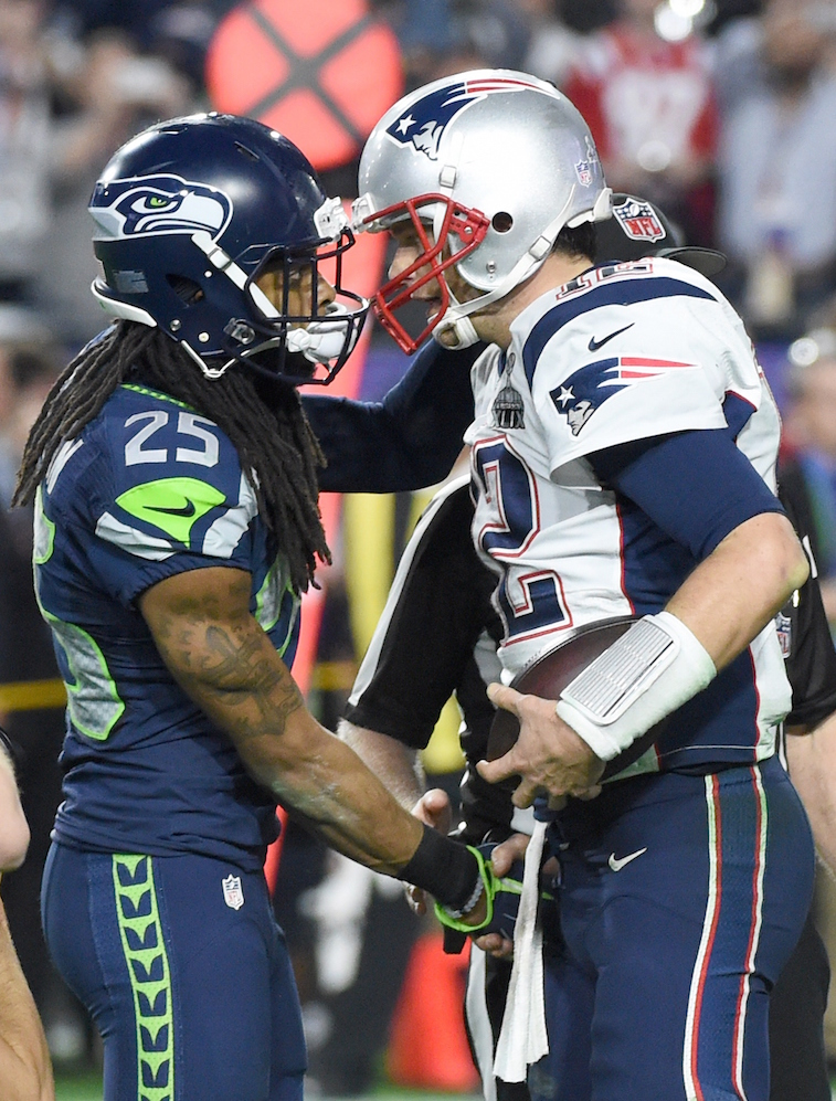 Richard Sherman of the Seattle Seahawks speaks with Tom Brady of the New England Patriots.