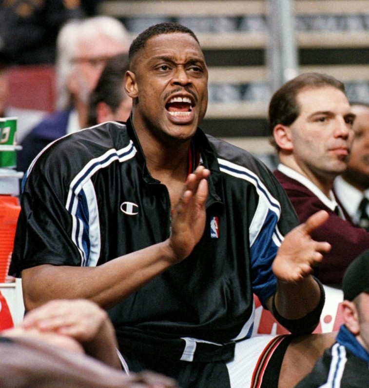 Rick Mahorn claps and shouts as he sits on the bench.