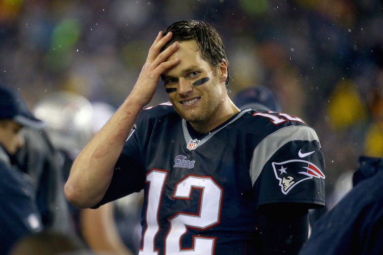Tom Brady laughs from the sidelines as he faces Tim Tebow's Denver Broncos.