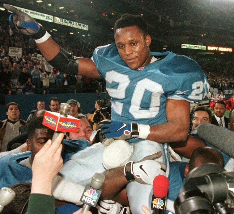 PONTIAC, : This 21 December 1997 file photo show Detroit Lions Barry Sanders as he is carried off of the field by his teammates after he became one of three players to rush for over 2,000 yards in a season against the New York Jets 21 December 1997 at the Pontiac, Mich, Silverdome. Sanders will reportedly announce his retirement from football after a 10-year career. AFP PHOTO Jeff KOWALSKY (Photo credit should read JEFF KOWALSKY/AFP/Getty Images)
