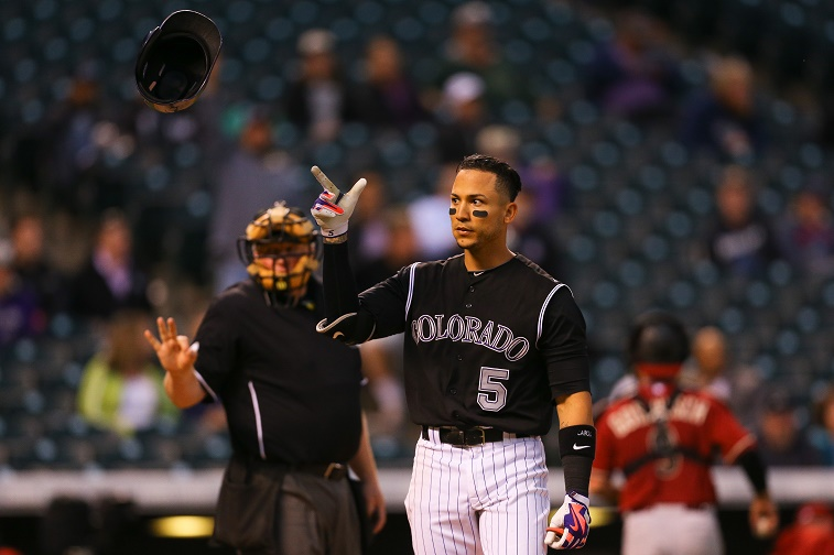 Carlos Gonzalez points up in the air.
