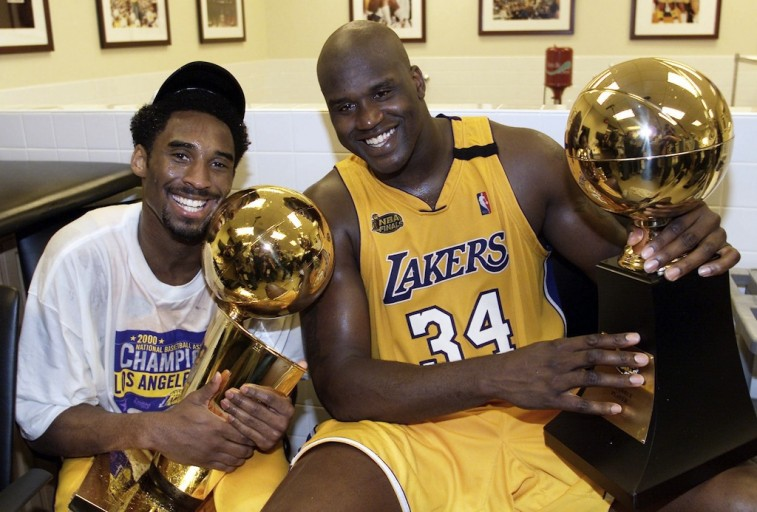 Kobe Byrant and Shaquille O'Neal pose together with trophies.