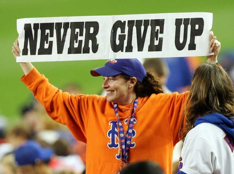 """New York Mets fan holds up """"Never Give Up"""" sign"""