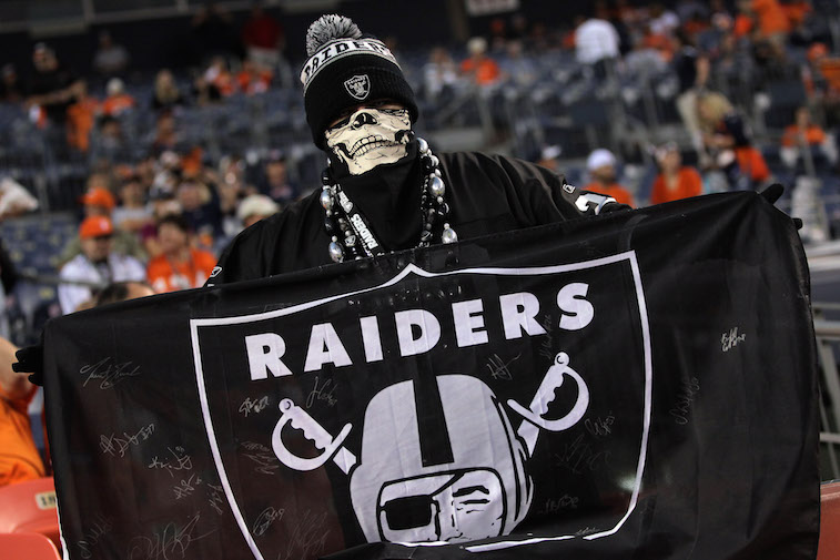 A Raiders fan holds up a flag.