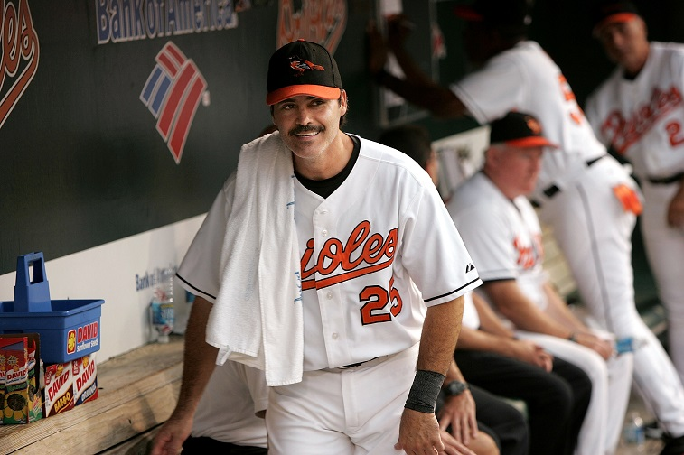 BALTIMORE - AUGUST 11: Rafael Palmeiro #25 of the Baltimore Orioles jokes with teammates in the dugout between innings against the Tampa Bay Devil Rays on August 11, 2005 at Oriole Park at Camden Yards in Baltimore, Maryland. Palmeiro returns from his 10-day suspension by Major League Baseball for violating the league's steroids policy after failing a drug test.