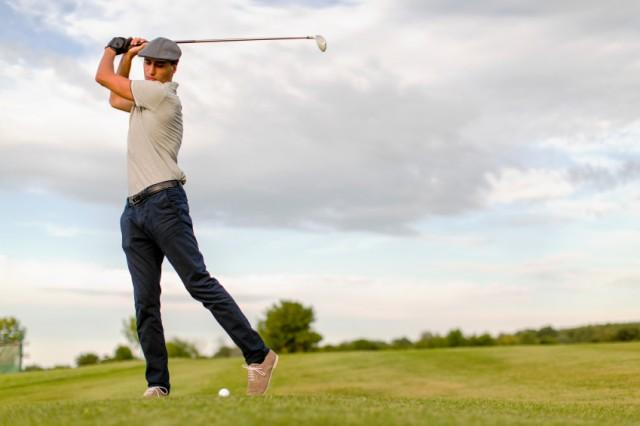 man swinging golf club at the course