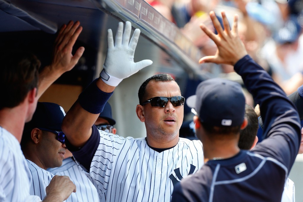 Alex Rodriguez high fives his teammates after hitting a home run.