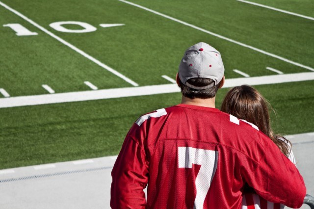 A couple stands in front of a football field.