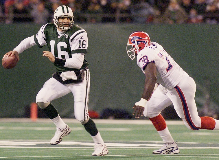 EASY RUTHERFORD, UNITED STATES: New York Jets quarterback Vinny Testaverde (L) scrambles away from Buffalo Bills defensive end Bruce Smith 08 November in East Rutherford, New Jersey. The Jets won 34-12.
