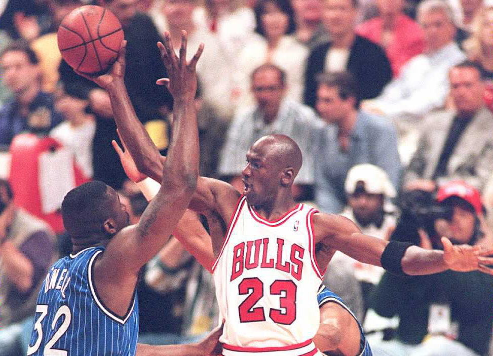 Michael Jordan of the Chicago Bulls passes the ball off under pressure from Orlando Magic center Shaquille O'Neal.