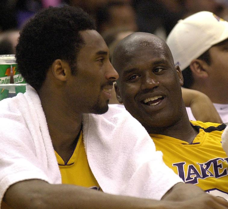 Shaquille O'Neal and Kobe Bryant laughing together while sitting on the bench.