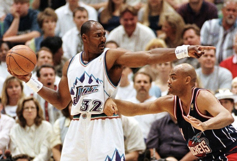 Karl Malone points at a teammate before he passes.