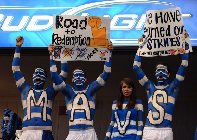 Fully painted Mavericks fans hold up signs from the nosebleeds.