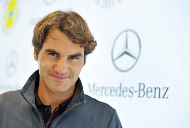 Roger Federer smiling on the red carpet of an event.