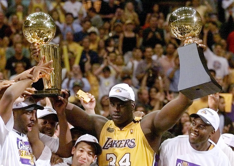 Shaq raises both the Larry O'Brien trophy and his MVP trophy after winning the 2000 championship.