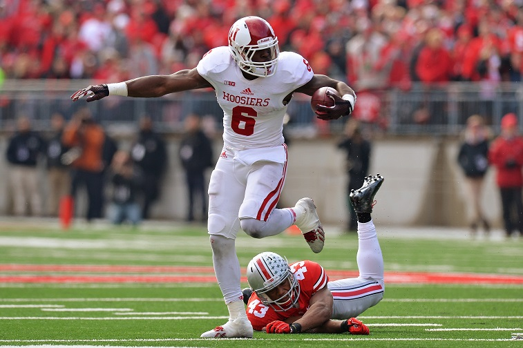 COLUMBUS, OH - NOVEMBER 22:  Tevin Coleman #6 of the Indiana Hoosiers leaps past the tackle attempt of Darron Lee #43 of the Ohio State Buckeyes in the second quarter at Ohio Stadium on November 22, 2014 in Columbus, Ohio. Coleman's three rushing touchdowns weren't not enough as Ohio State defeated Indiana 42-27.