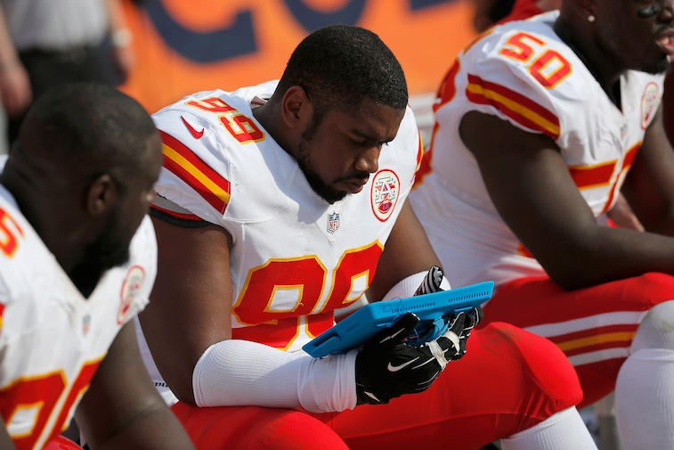 Vance Walker #99 of the Kansas City Chiefs consults a person electronic device