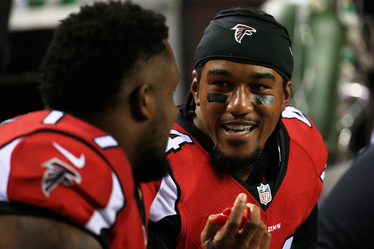 Vic Beasley (#44) talks to a teammate on the sidelines during a preseason game against the Tennessee Titans