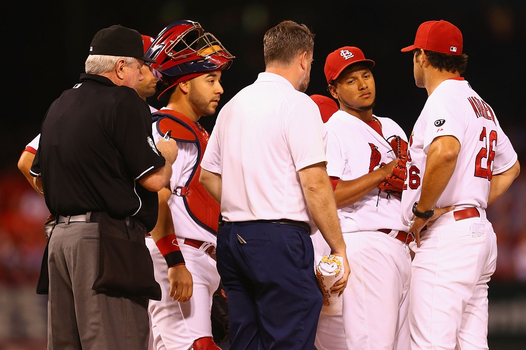 ST. LOUIS, MO - SEPTEMBER 25: Starter Carlos Martinez #18 of the St. Louis Cardinals meets with manager Mike Matheny #26 and a member of the training staff in the first inning against the Milwaukee Brewers at Busch Stadium on September 25, 2015 in St. Louis, Missouri.  Martinez was removed from the game with shoulder tightness.