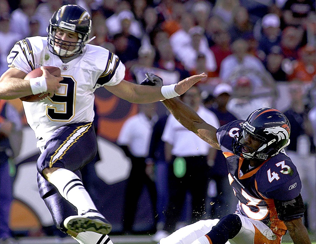 DENVER, : San Diego Chargers' quarterback Drew Brees escapes being sacked by Denver Bronco Izell Reese during their 06 October, 2002, game at Invesco Field in Denver, Colorado.
