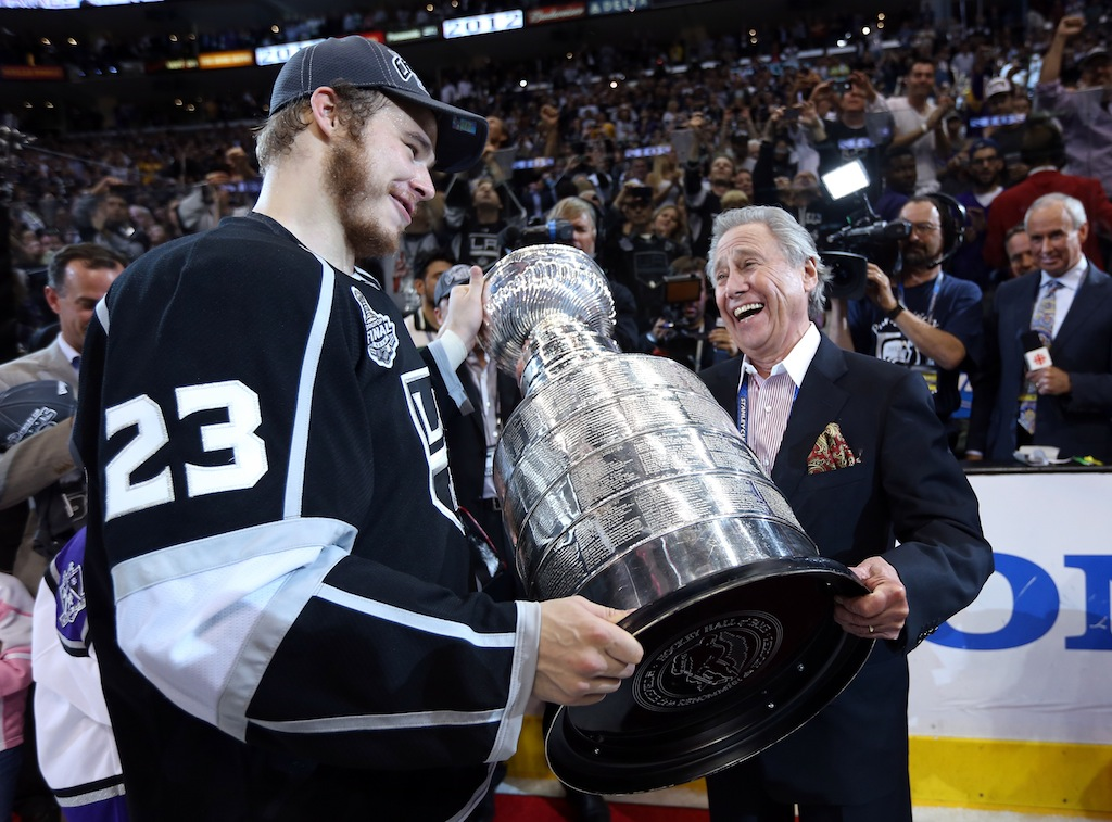 Dustin Brown hands over the Stanley Cup to Kings team owner Philip Anschutz