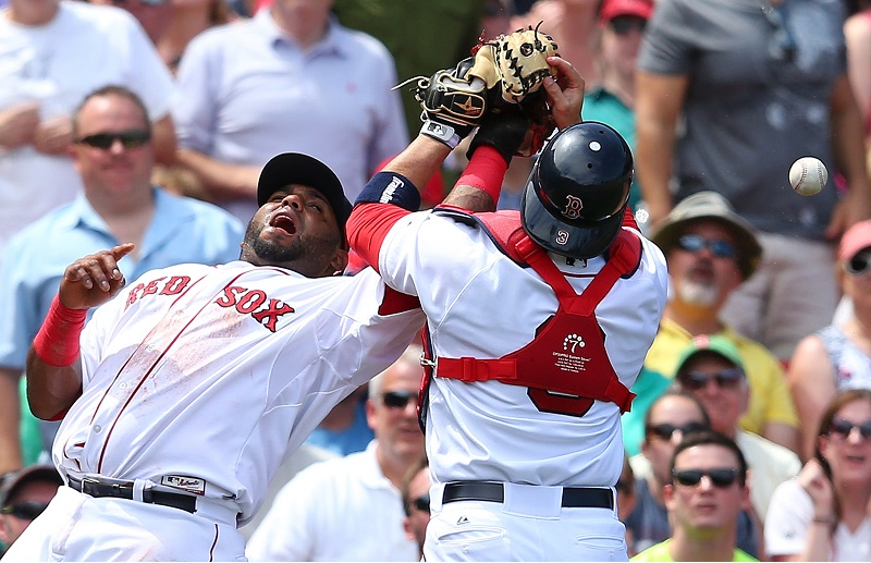 Pablo Sandoval (L) of the Boston Red Sox and Sandy Leon collide and fail to catch a foul