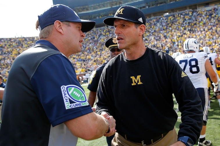 Head coach Jim Harbaugh (R) of the Michigan Wolverines greets head coach Bronco Mendenhall (L) of the Brigham Young Cougars at midfield after their game