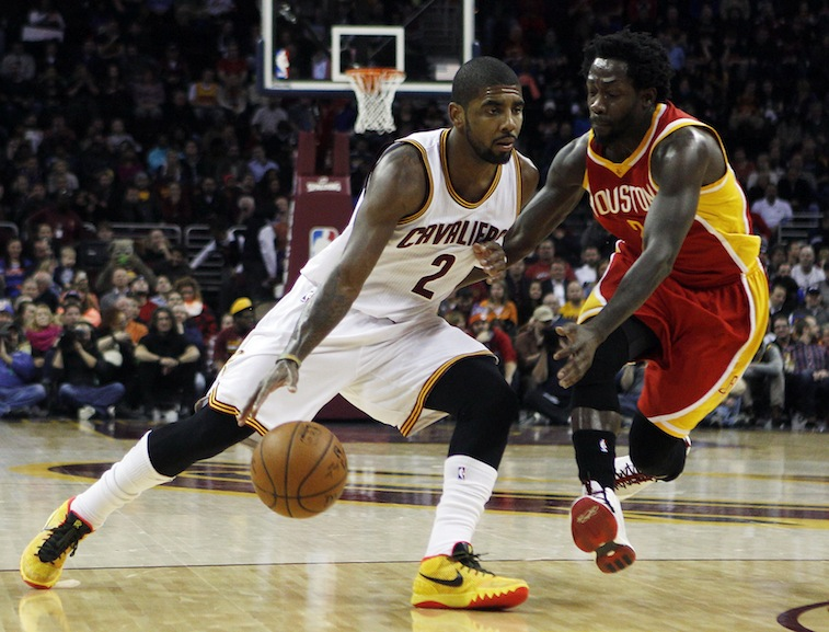 Kyrie Irving looks to dribble past Patrick Beverley