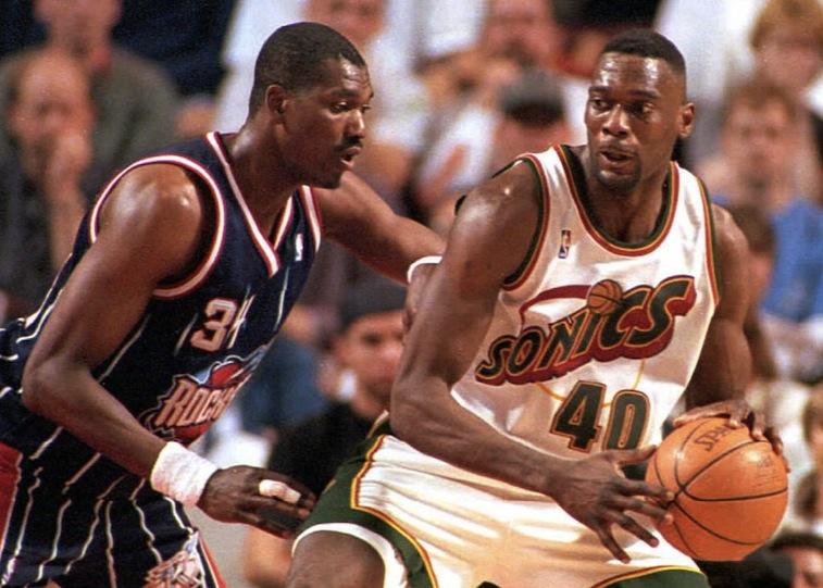 Seattle SuperSonics' Shawn Kemp tries pass Houston Rockets' Hakeem Olajuwon.