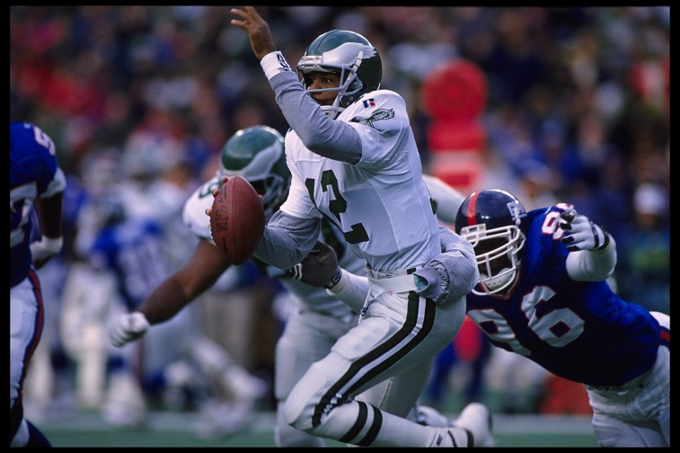 19 Nov 1995:   Quarterback Randall Cunningham #12 of the Philadelphia Eagles scrambles out of the pocket and tries to avoid a diving Jamal Duff #96 of the New York Giants during the Eagles 28-19 victory over the Giants at Veterans Stadium in Philadelphia,