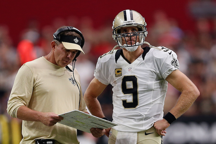 Sean Payton and Drew Brees talk on the sidelines during a game.