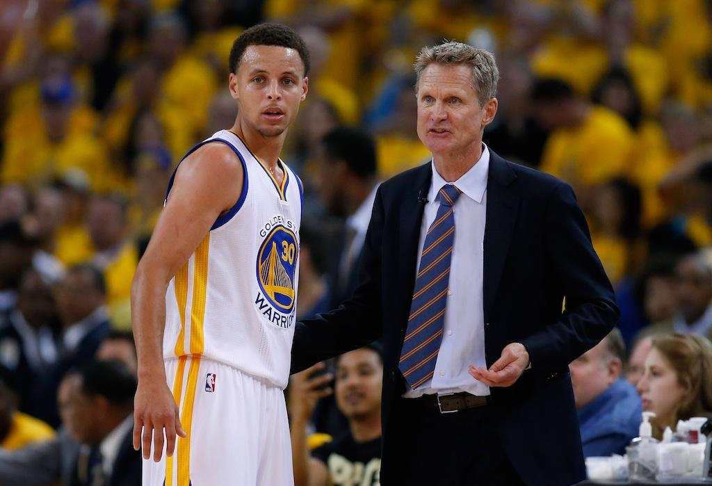 Stephen Curry (R) talks with head coach Steve Kerr