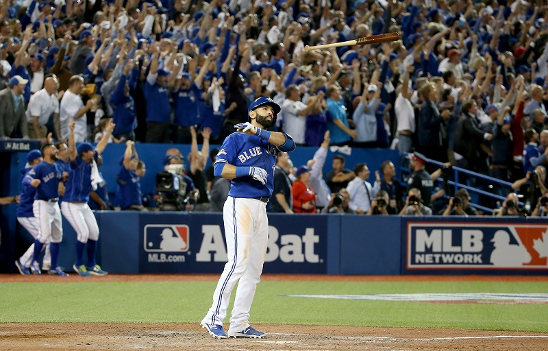 Jose Bautista of the Toronto Blue Jays throws his bat up in the air after he hits a three-run home run.
