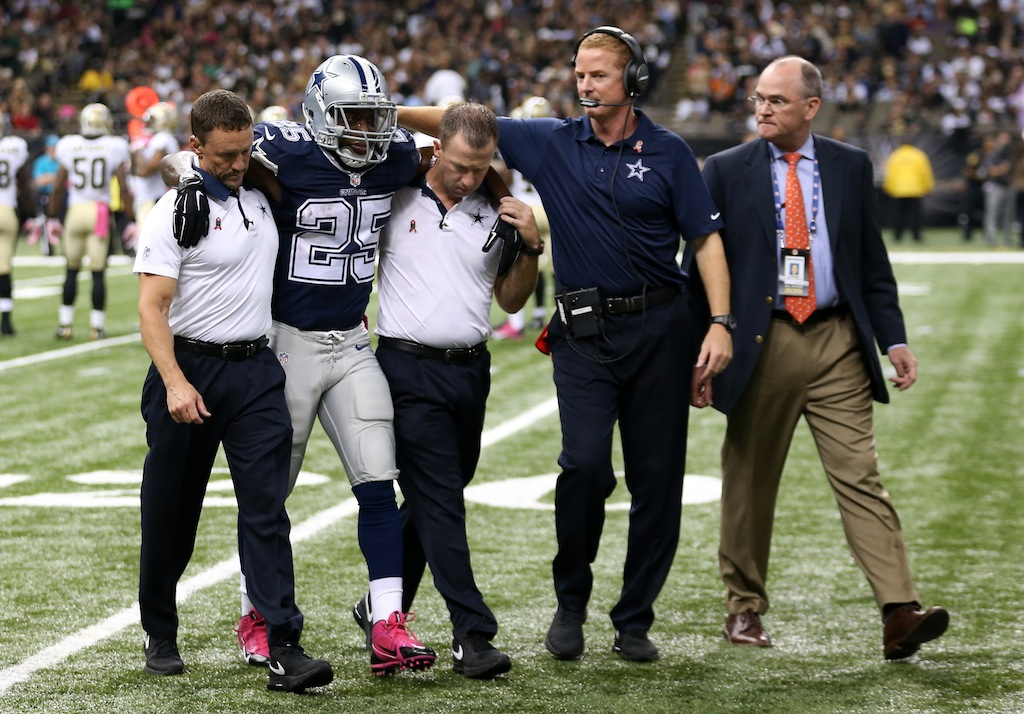 Lance Dunbar of the Dallas Cowboys is helped off the field