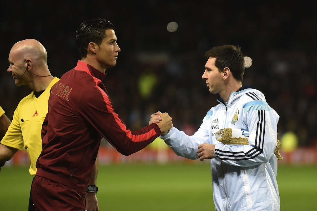 Cristiano Ronaldo (L) and Lionel Messi (R) shakes hands prior to a match between their two teams