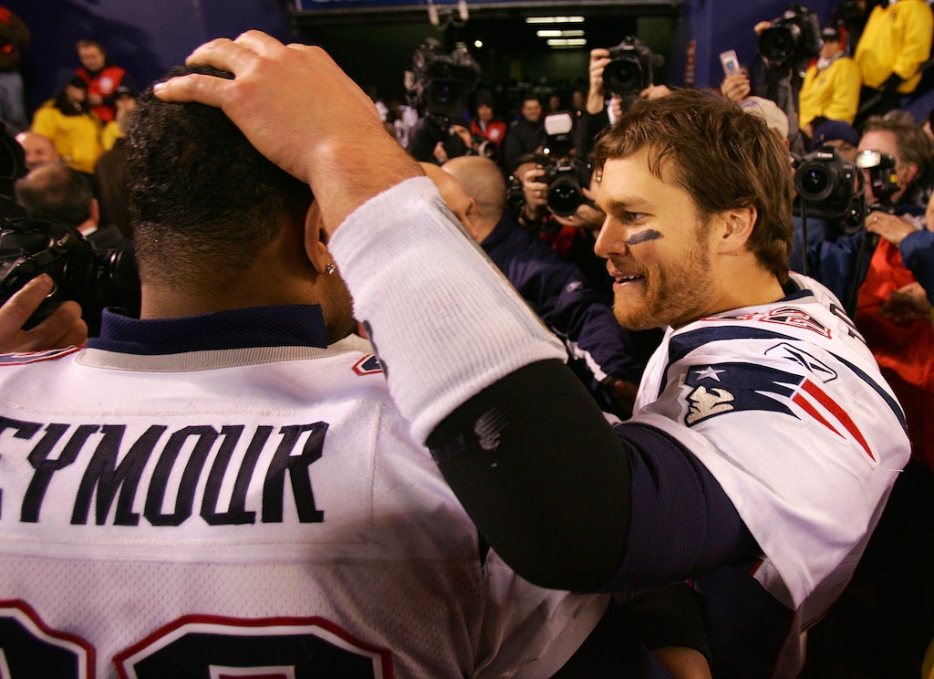Tom Brady #12 of the New England Patriots celebrates with Richard Seymour #93 after defeating the New York Giants to go undefeated for the season