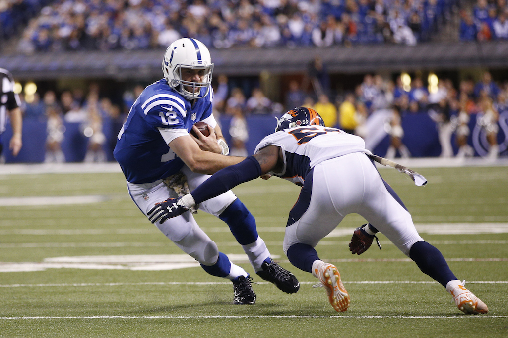 Andrew Luck is hit while scrambling against the Broncos