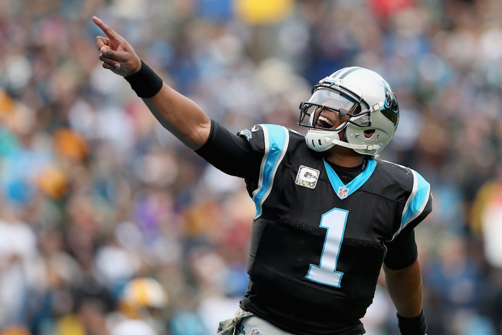 Cam Newton celebrates a rushing touchdown against the Packers