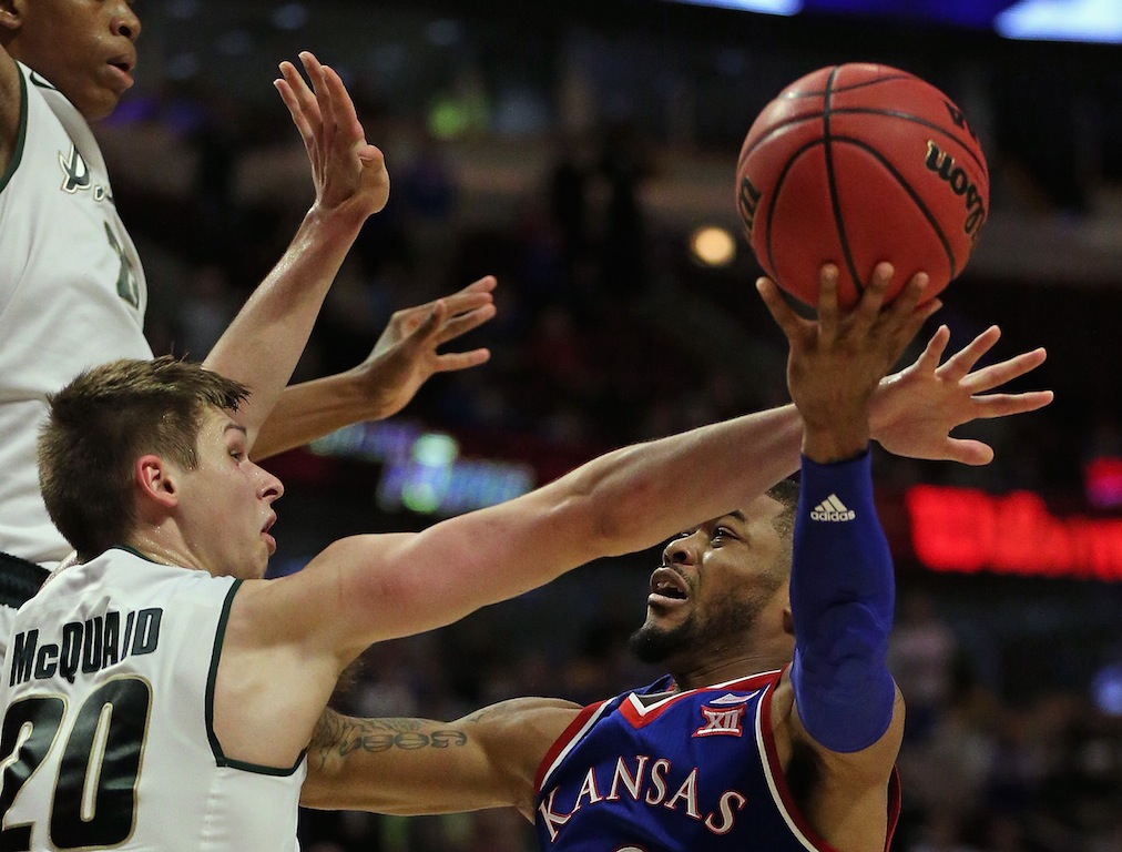 Frank Mason III #0 of the Kansas Jayhawks goes up for a shot against Matt McQuaid #20 of the Michigan State