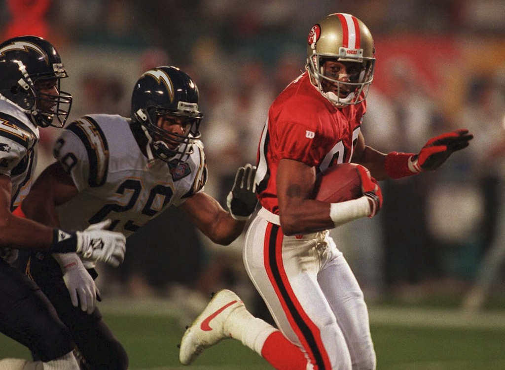 DOUG COLLIER/AFP/Getty Images MIAMI, FL - JANUARY 29: San Francisco 49er wide receiver Jerry Rice (R) runs past San Diego Chargers Stanley Richard (L) and Darren Carrington (C) to score a first-quarter touchdown 29 January 1995 during Super Bowl XXIX at Joe Robbie Stadium in Miami. The touchdown was the earliest scored in Super Bowl history at 1:24 into the game. (COLOR KEY: Rice jersey red.) AFP PHOTO (Photo credit should read DOUG COLLIER/AFP/Getty Images)