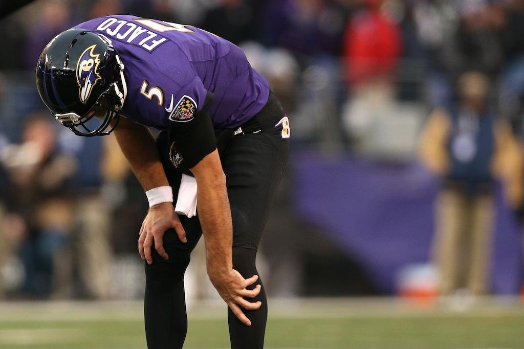 Joe Flacco holds his knee in pain