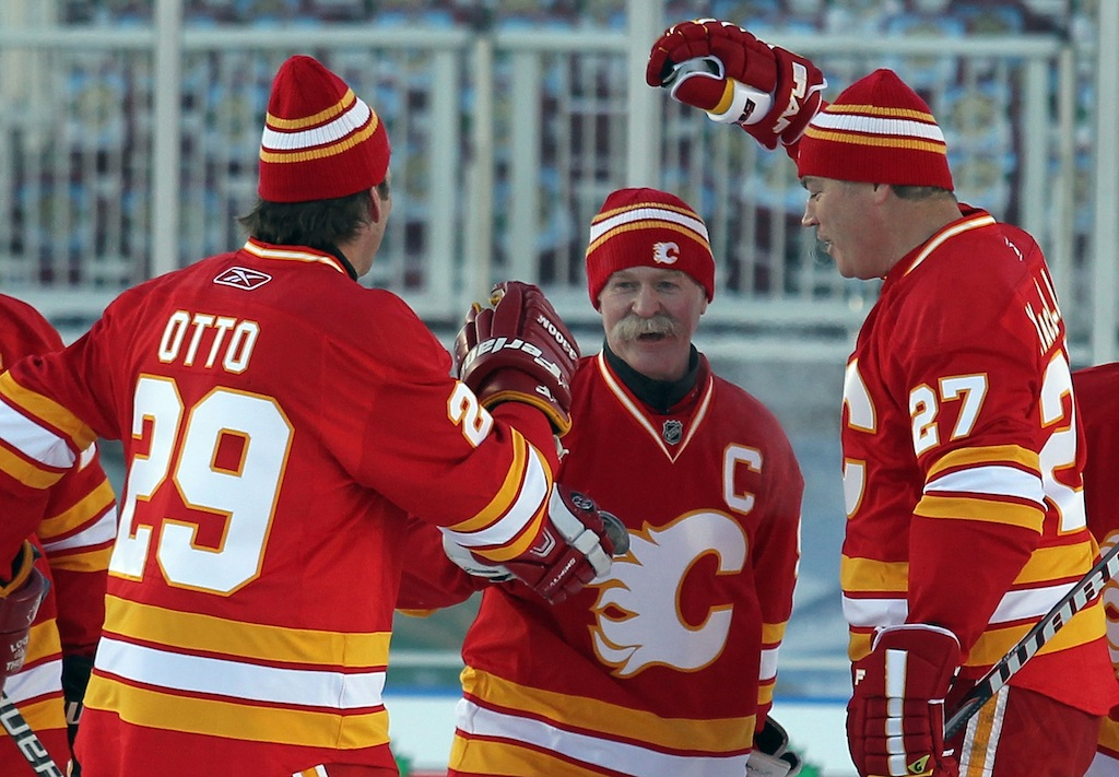 Joel Otto #29 (L) and Brian MacLellan #27 (R) congratulate Lanny McDonald #9 (C) of the Calgary Flames Alumni on his penalty shot goal