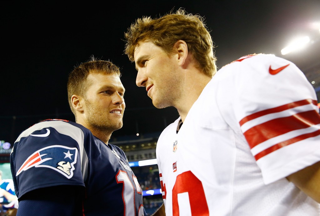 Tom Brady and Eli Manning greet each other on the field.