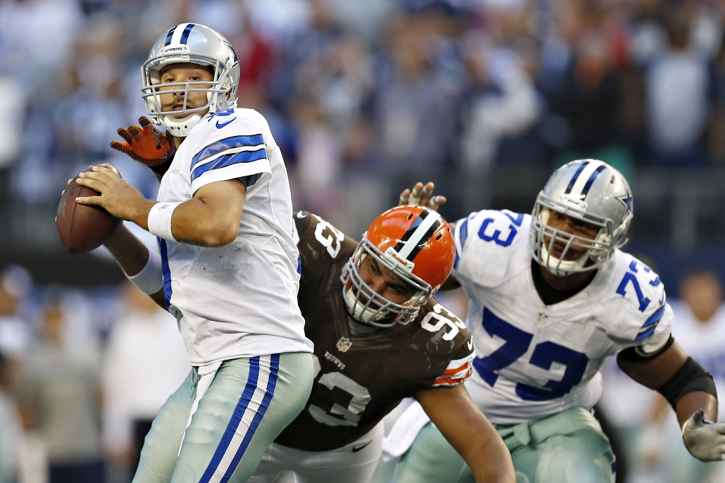 ARLINGTON, TX - NOVEMBER 18: Tony Romo #9 of the Dallas Cowboys looks downfield for a receiver under pressure from John Hughes #93 of the Cleveland Browns at Cowboys Stadium on November 18, 2012 in Arlington, Texas. The Cowboys defeated the Browns 23-20