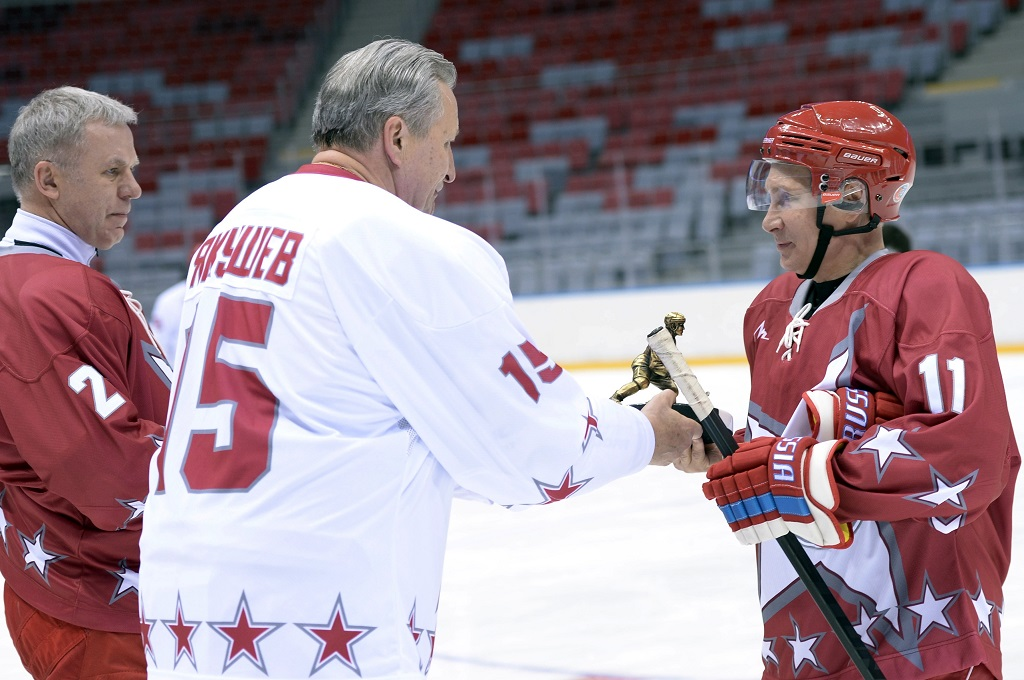 Russian President Vladimir Putin (R) salutes hockey stars Vyacheslav Fetisov (L) and Alexander Yakushev (C) during a hockey game with the stars of the Soviet hockey in Sochi on January 4, 2014.
