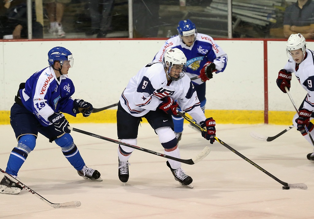 LAKE PLACID, NY - AUGUST 04: Auston Matthews #19 of USA White moves the puck around Saku Kinnunen #18 of Team Finland during the 2014 USA Hockey Junior Evaluation Campat Lake Placid Olympic Center on August 4, 2014 in Lake Placid, New York