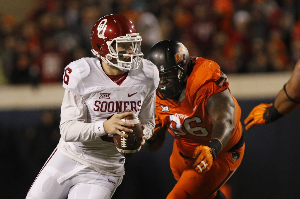 STILLWATER, OK - NOVEMBER 28 : Quarterback Baker Mayfield #6 of the Oklahoma Sooners scrambles under pressure from defensive tackle Vincent Taylor #96 of the Oklahoma State Cowboys November 28, 2015 at Boone Pickens Stadium in Stillwater, Oklahoma. Oklahoma defeated Oklahoma State 58-23.