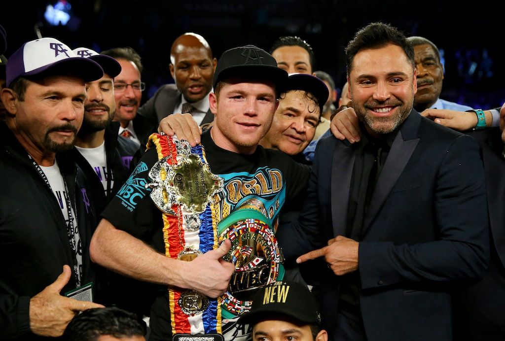Canelo Alvarez celebrates with promoter Oscar De La Hoya after defeating Miguel Cotto by unanimous decision in their middleweight fight