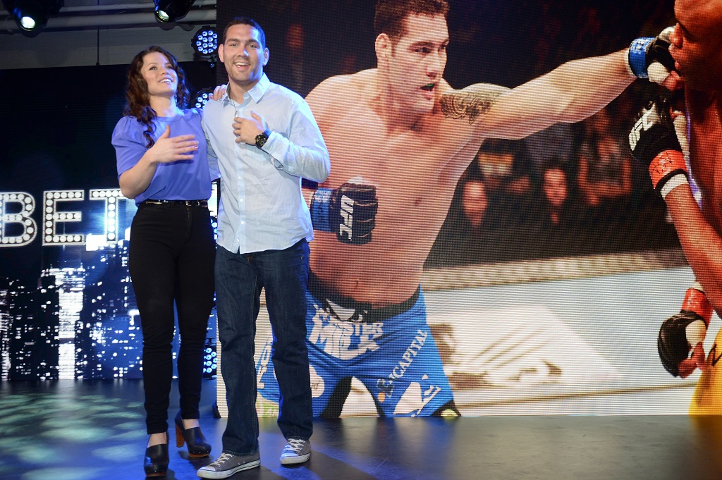 NEW YORK, NY - JANUARY 29: UFC Middleweight Champion Chris Weidman (R) and Time Warner Cable Studios host, Camille Ford appear onstage during the Time Warner Cable Studios UFC and Revolt taping at Time Warner Cable Studios on January 29, 2014 in New York City.