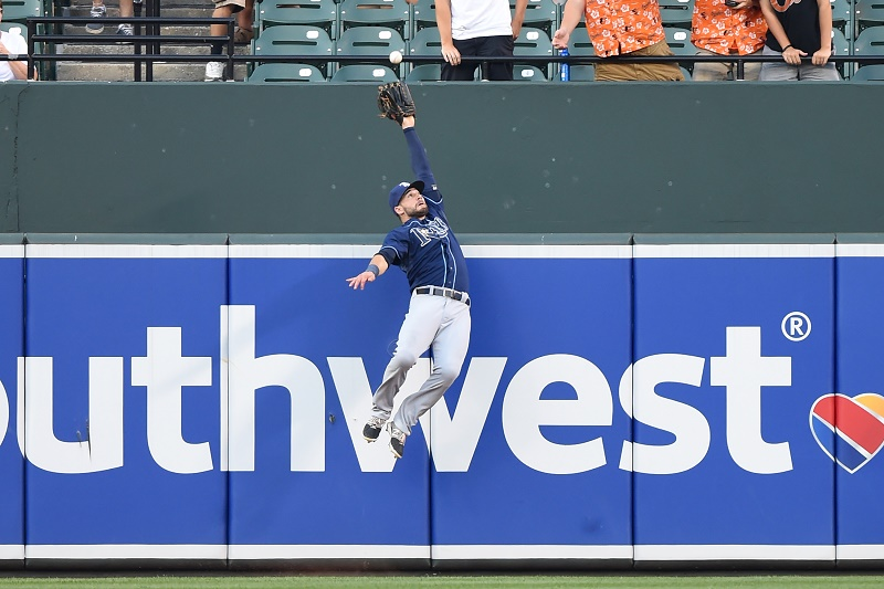 Kevin Kiermaier leaps into the air to catch the ball and prevent a home run.